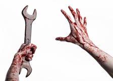 Main ensanglantée tenant une grande clé, clé ensanglantée, grande clé, thème ensanglanté, thème de Halloween, mécanicien fou, fon Photographie stock libre de droits
