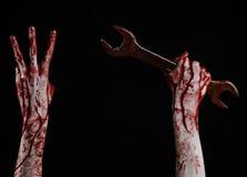 Main ensanglantée tenant une grande clé, clé ensanglantée, grande clé, thème ensanglanté, thème de Halloween, mécanicien fou, fon Photo libre de droits