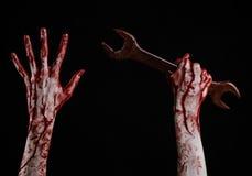 Main ensanglantée tenant une grande clé, clé ensanglantée, grande clé, thème ensanglanté, thème de Halloween, mécanicien fou, fon Images stock