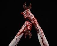 Main ensanglantée tenant une grande clé, clé ensanglantée, grande clé, thème ensanglanté, thème de Halloween, mécanicien fou, fon Images libres de droits