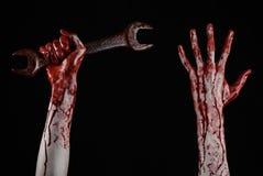 Main ensanglantée tenant une grande clé, clé ensanglantée, grande clé, thème ensanglanté, thème de Halloween, mécanicien fou, fon Photos libres de droits