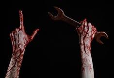 Main ensanglantée tenant une grande clé, clé ensanglantée, grande clé, thème ensanglanté, thème de Halloween, mécanicien fou, fon Photo stock