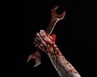 Main ensanglantée tenant une grande clé, clé ensanglantée, grande clé, thème ensanglanté, thème de Halloween, mécanicien fou, fon Photographie stock