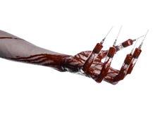 Main ensanglantée avec la seringue sur les doigts, seringues d'orteils, seringues de main, main ensanglantée horrible, thème de H Photos stock