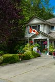 Main entrance of family house with canadian flag in front. Fragment of residential house with concrete driveway royalty free stock images