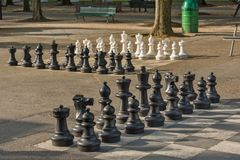 Public chess games in Bastions Park, Geneva. The main entrance to Bastions Park is from Place Neuve. Just behind the big decorated gate are huge black-white Royalty Free Stock Photo