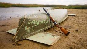Main equipment of undemanding ducks hunter - canoe and shotgun Stock Image