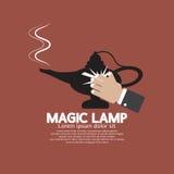 Main essuyant la lampe magique Photographie stock