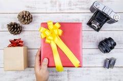 Main et conception actuelle de boîte-cadeau enveloppées en papier de couleur avec l'arc Images libres de droits