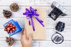 Main et conception actuelle de boîte-cadeau enveloppées en papier de couleur avec l'arc Photo libre de droits