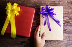 Main et conception actuelle de boîte-cadeau enveloppées en papier de couleur avec l'arc Photos stock
