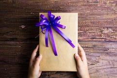 Main et conception actuelle de boîte-cadeau enveloppées en papier de couleur avec l'arc Image libre de droits