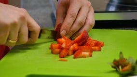 Main et couteau de chef coupant en tranches la fraise fraîche sur la planche à découper image libre de droits