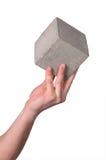 Main et cube Photos stock