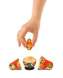 Main et matrioska russe de jouet Photo stock