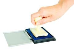 Main et tampon en caoutchouc sur une protection bleue Photo stock
