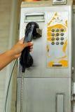 Main et vieille cabine de téléphone de vintage Image stock