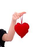 Main féminine retenant un coeur rouge Images stock