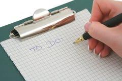 Main femelle écrivant POUR FAIRE la liste Images stock