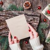 Main femelle écrivant une lettre à Santa sur le fond en bois avec des cadeaux de Noël, texture d'écorce, branches de sapin photo stock
