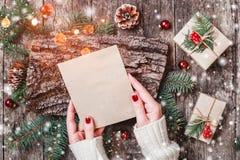 Main femelle écrivant une lettre à Santa sur le fond en bois avec des cadeaux de Noël, texture d'écorce, branches de sapin image libre de droits