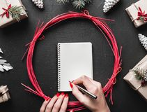 Main femelle écrivant une lettre sur le fond noir avec des cadeaux de Noël, des branches de sapin, des cônes de pin et des décora Images libres de droits
