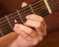 Main femelle apprenant la corde de guitare Image stock