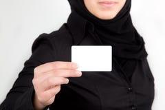 Main femelle arabe retenant le businesscard blanc Photos stock