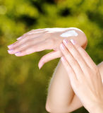 Main femelle avec de la crème cosmétique là-dessus Image libre de droits