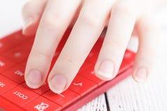 Main femelle avec la calculatrice photos stock