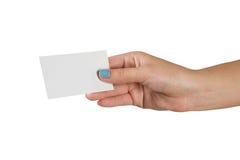 Main femelle avec la manucure multicolore jugeant une carte de visite professionnelle vierge de visite d'isolement sur le fond bl Photo stock