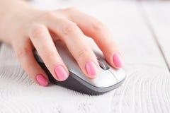 Main femelle avec la souris d'ordinateur sur la table, plan rapproché image stock