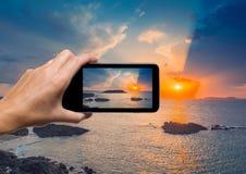 Main femelle avec le smartphone prenant une photo de beau coucher du soleil Photos libres de droits