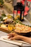 Main femelle avec le verre de vin, pizza à l'arrière-plan photo libre de droits