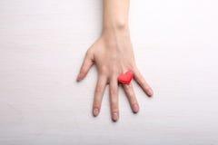 Main femelle avec peu de coeur sur le doigt sur le backgrou léger Photographie stock