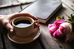 Main femelle avec une tasse de café, de livre et de fleurs sur le fond en bois Fleurs, coupure, travail Photos stock