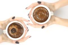 Main femelle avec une tasse de caf? noir sur le dessus de table blanc images stock