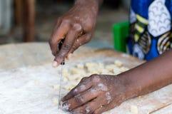Main femelle coupant une pâte de farine photos stock