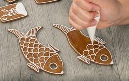 Main femelle décorant les pains d'épice cuits au four dans la forme de poissons photographie stock