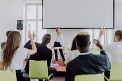 Main femelle d'augmenter des employés posant la question à la femme d'affaires faisant la présentation de flipchart Jeune femme r photo libre de droits