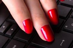 Main femelle dactylographiant sur le clavier d'ordinateur portable Photos stock