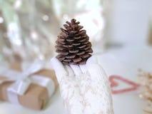 Main femelle dans des mitaines tricotées blanches avec le grand cône de pin sur le fond d'hiver de Noël photos libres de droits