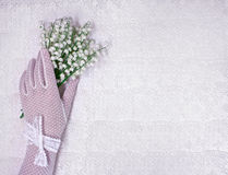 Main femelle dans les gants blancs avec un bouquet des lis du vall photographie stock