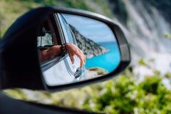 Main femelle de Brown dans le miroir de vue de côté de voiture La mer Méditerranée bleue et roches blanches à l'arrière-plan image stock