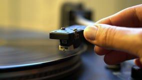 Main femelle de tourne-disque de plaque tournante de vinyle de vintage de boucle de Cinemagraph tenant le niddle clips vidéos