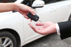 Main femelle donnant une clé pour l'acheteur ou la voiture de location photos libres de droits