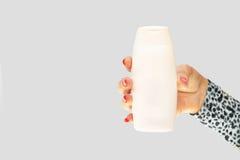 Main femelle du ` s avec les clous rouges tenant une bouteille en plastique blanche Images libres de droits