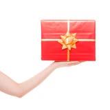 Main femelle jugeant le grand boîte-cadeau rouge d'isolement Photo stock