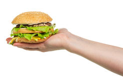 Main femelle jugeant un hamburger d'isolement sur le blanc photographie stock