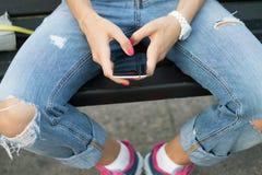 Main femelle jugeant un téléphone portable en gros plan Image stock